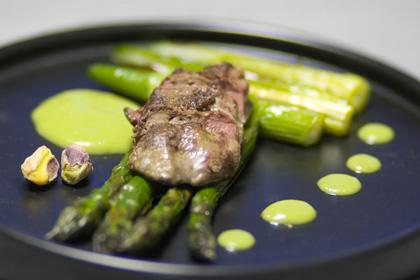 Glaserad sparris med kycklinglever och sås på gröna ärtor